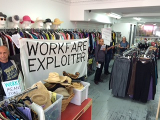"photo of protestors inside nlh shop - banner ""workfare exploiter"""